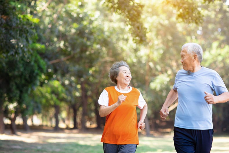 A senior couple jogging together along a community trail on a sunny day
