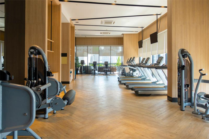 modern fitness center and exercise equipment indoors with windows