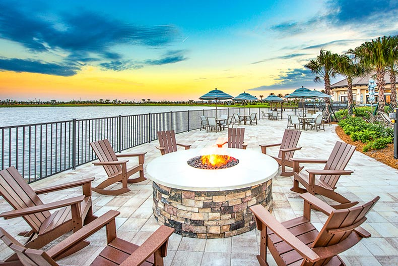 A ring of deck chairs encircling a patio fire pit at sunset at Del Webb Lakewood Ranch in Lakewood Ranch, Florida