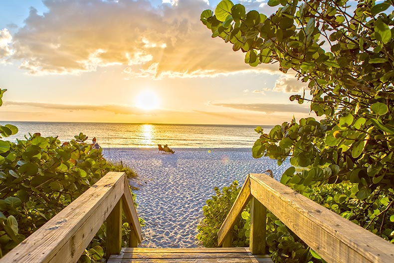 View of a beach beyond a wooden boardwalk at sunset in Naples, Florida
