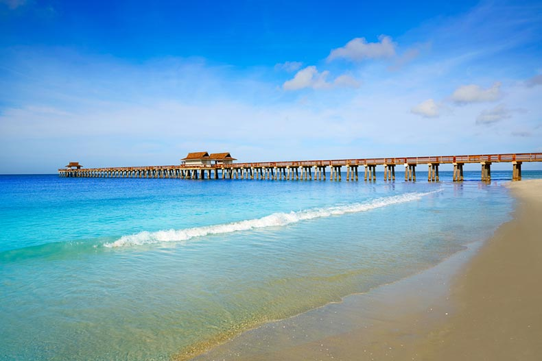 View of Naples Pier and beach in Florida on a sunny day