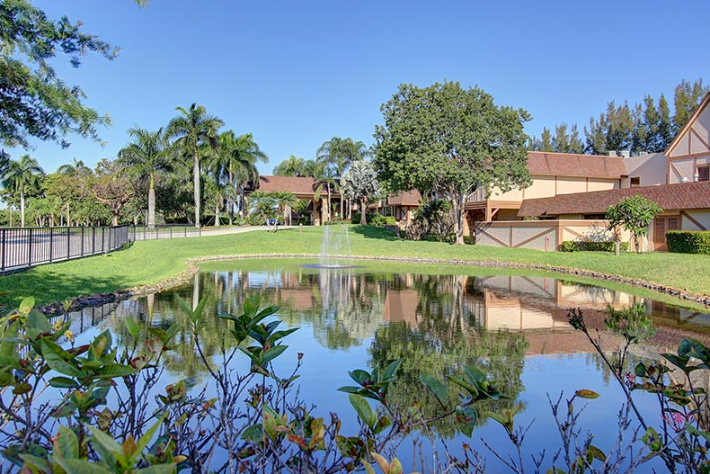 View of a pond with a water feature at Huntington Lakes in Delray Beach, Florida