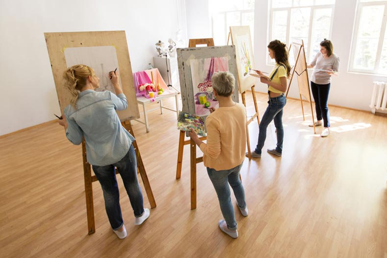 A group of woman artists painting and drawing on easels in an art studio
