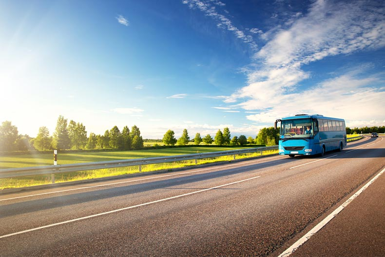 A blue bus driving down an asphalt road surrounded by green countryside