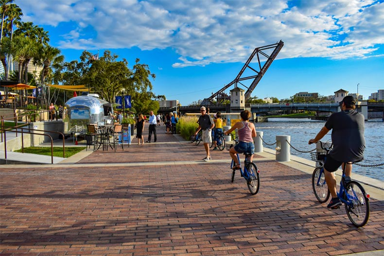 People biking and walking on the riverwalk in the downtown area of Tampa Bay, Florida