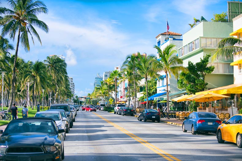 Early morning view down Ocean Drive lined with palm trees and Art Deco hotels in Miami, Florida