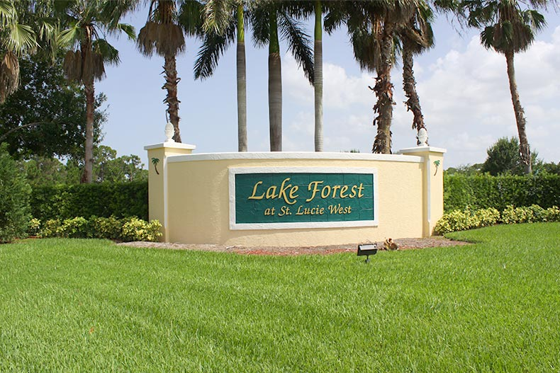 Palm trees and fresh-cut grass surrounding the community sign for Lake Forest in Port St. Lucie, Florida