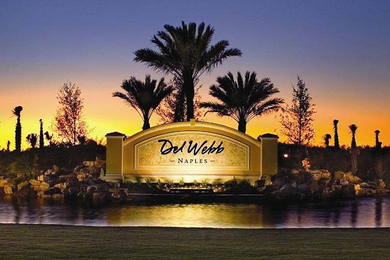 Sunset view of the community sign for Del Webb Naples with palm trees in the background