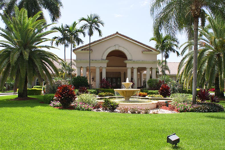 Exterior view of the manicured landscaping outside the clubhouse at The Cascades in Boynton Beach, Florida