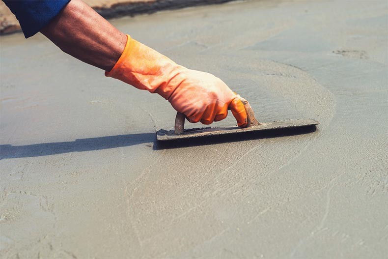 Closeup on a hand leveling concrete at a construction site