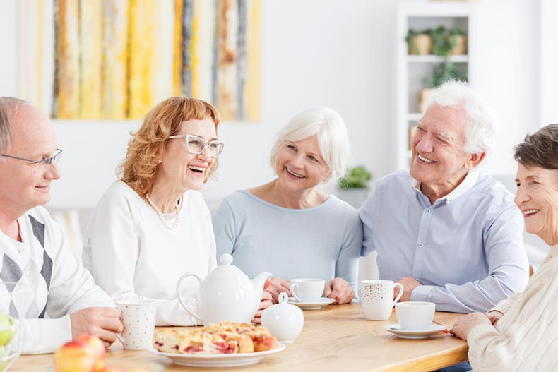 A club of happy older people meeting over tea and pastries