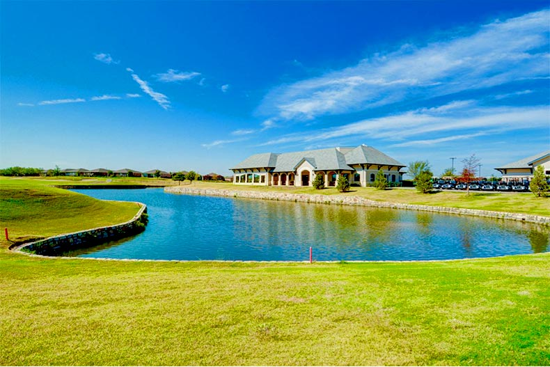 View across a pond of the Frisco Lakes clubhouse in Frisco, Texas