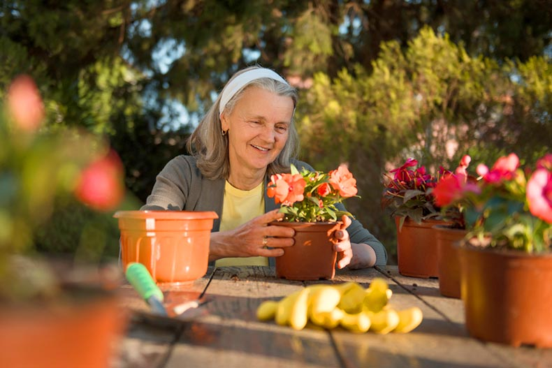 A senior woman sitting at a wooden table and smiling while potting flowers