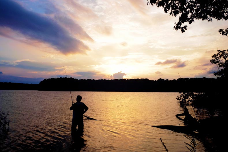fisherman standing in Lake Benson at sunset in Garner, North Carolina