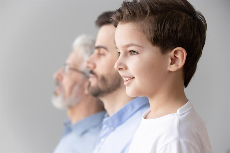 A young boy looking forward as he stands in a row with his father and grandfather