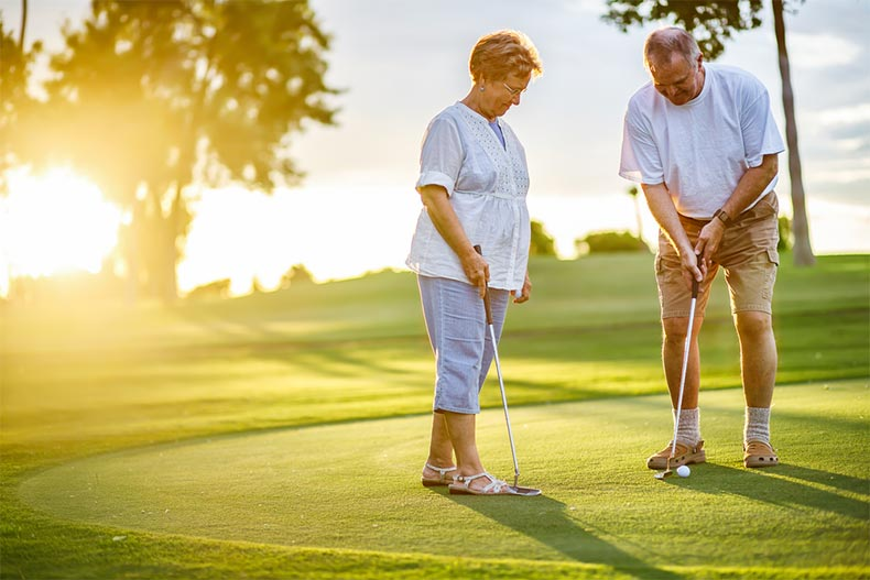 Active adult couple golfing at sunset
