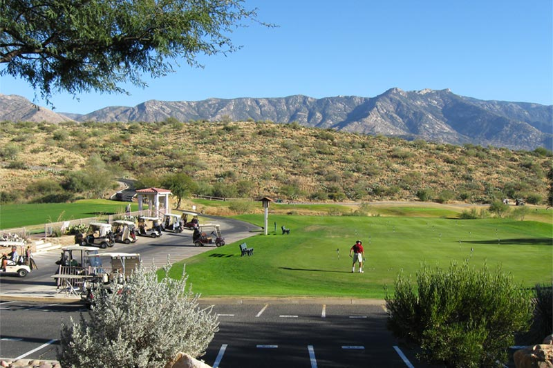 man teeing up at arizona golf course with mountains in background