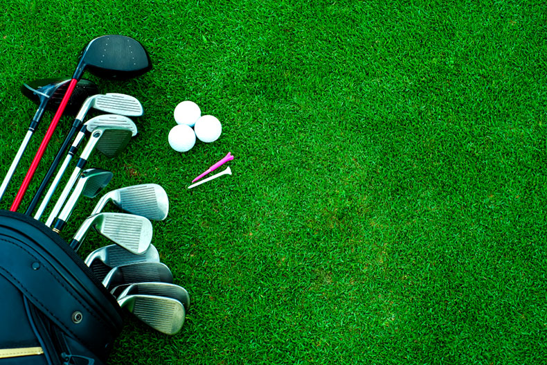Golf clubs, balls, and tees on the grass of a golf course.