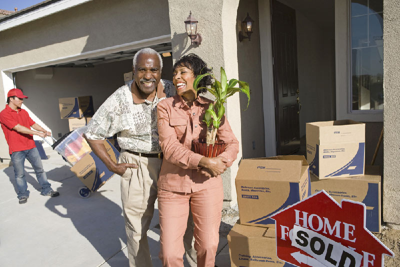 couple moving out of home smiling with movers in the background