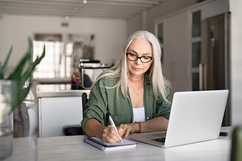 An older woman taking notes while browsing homes for sale online