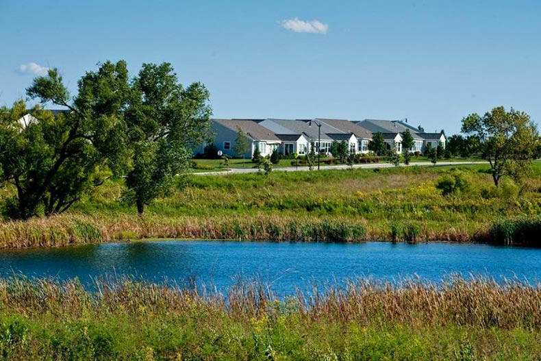 A pond surrounded by prairie and modern homes at Grand Dominion in Mundelein, Illinois