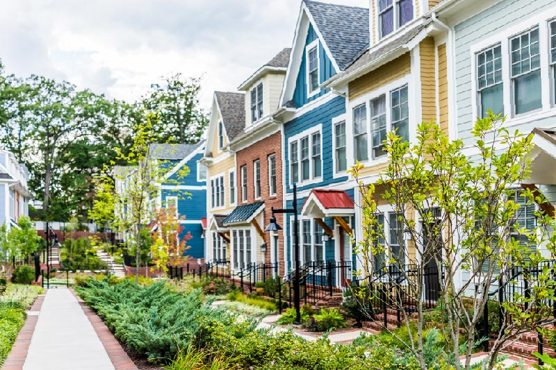 row of colorful homes with lush greenery and community gardens