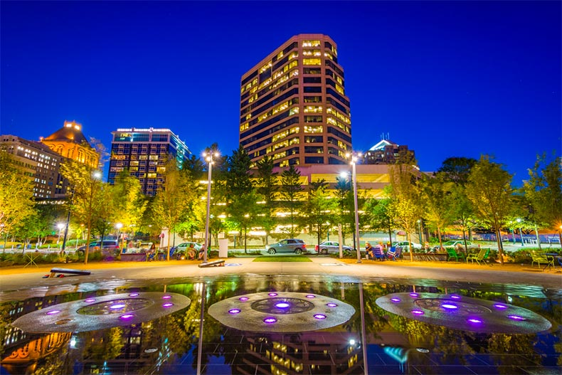 A nighttime view of a park with buildings in the background in North Carolina's Piedmont Triad cities