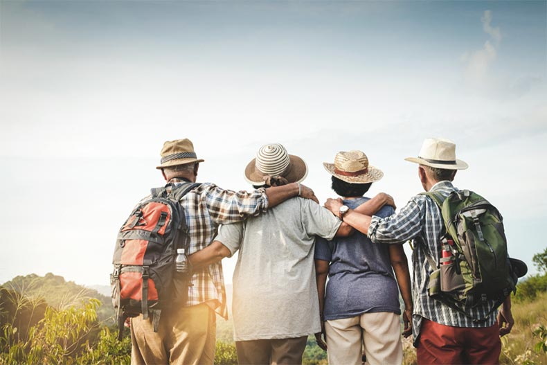A group of older adults with their backs to the camera linking arms and looking towards the sunset
