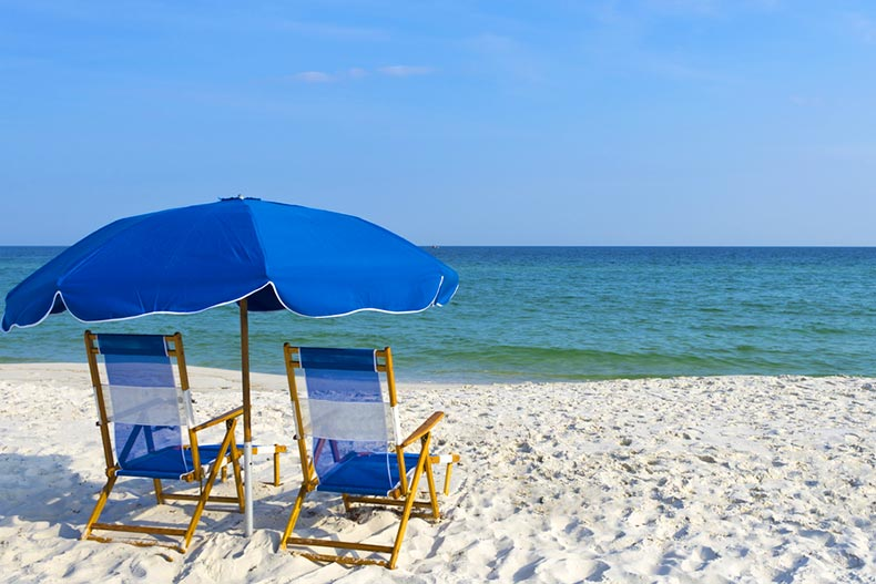 Two beach chairs under an umbrella on a picturesque Gulf Coast beach
