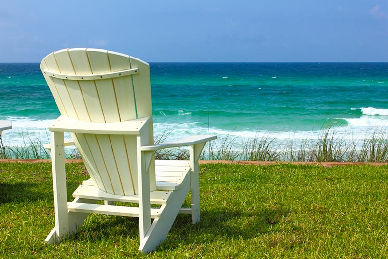 Adirondack chair on grass looking out onto beach and Gulf of Mexico