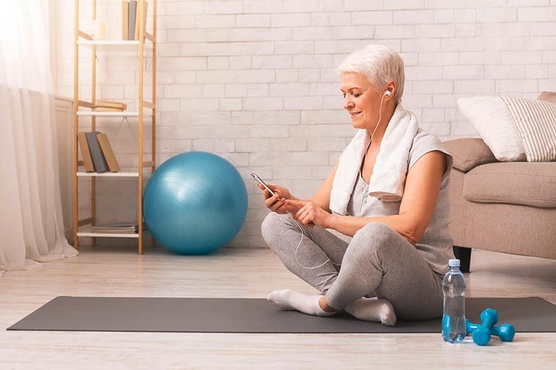 An older woman with a towel around her shoulders sitting on a yoga mat while selecting music on her smart phone