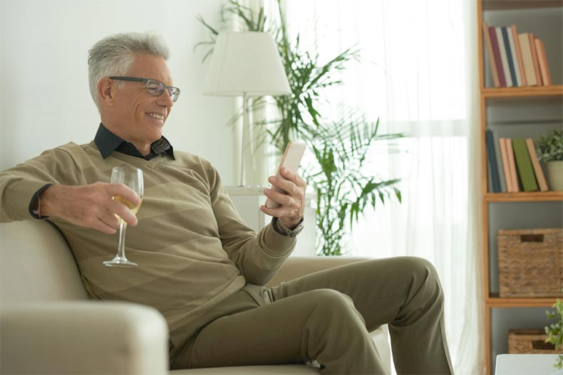 An older man smiling and video chatting on his phone while drinking wine