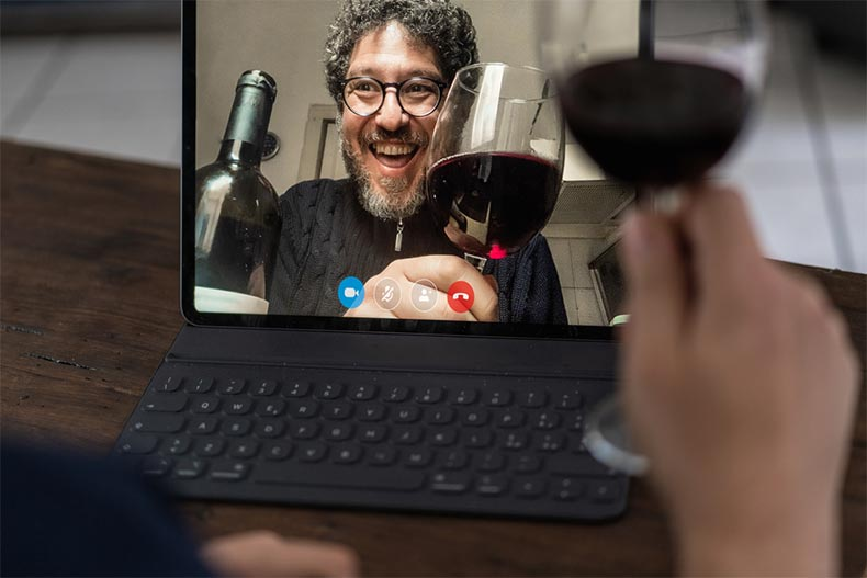 Two older adult friends toasting with red wine while video chatting