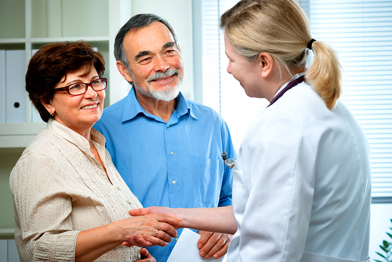 Retired couple shaking hands with a doctor.