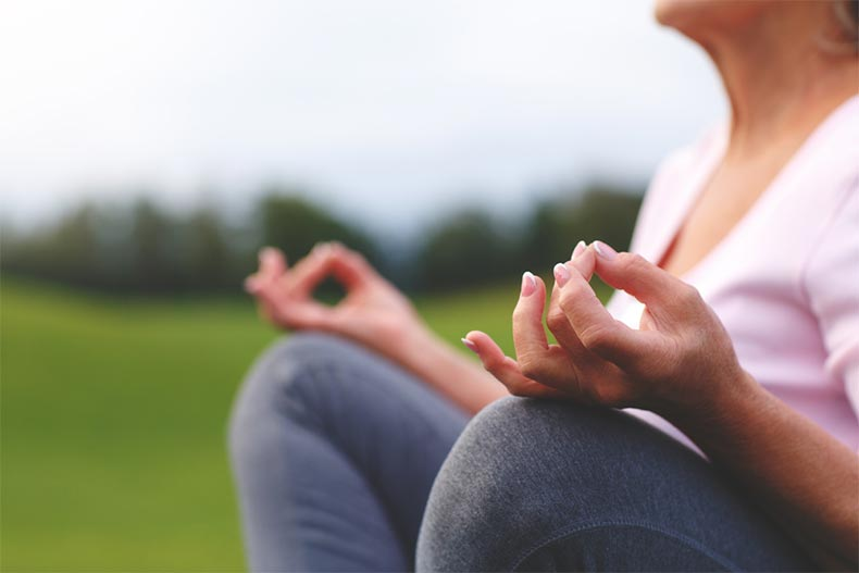 Closeup on the hands of a senior woman as she meditates while practicing yoga