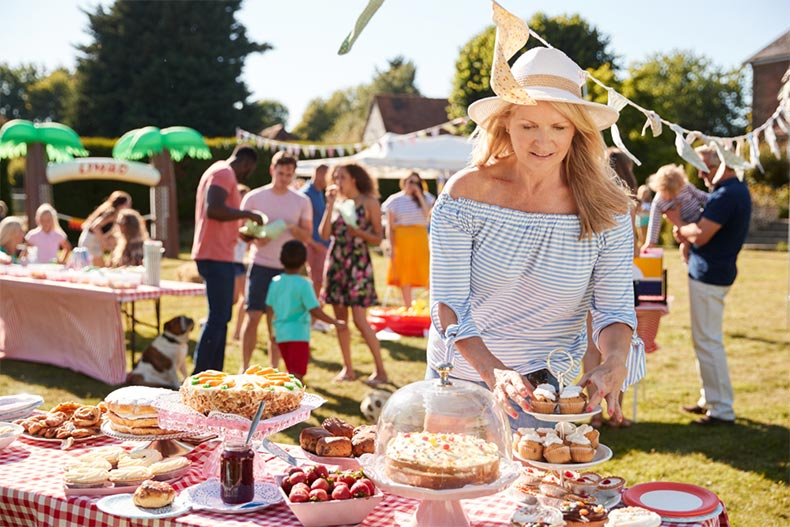 A senior woman organizing an outdoor picnic for a fundraising event