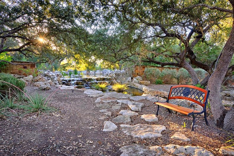 A bench surrounded by trees in a picturesque area at Hill Country Retreat in San Antonio, Texas