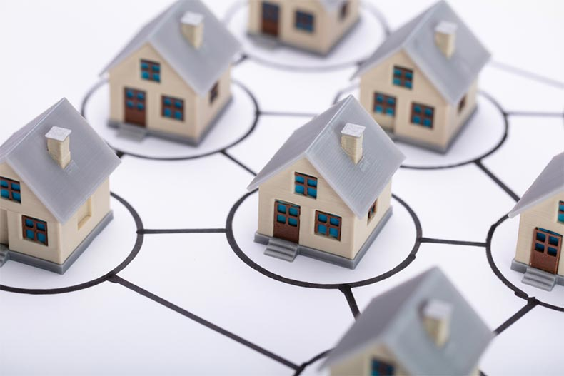 Small, plastic house modes in circles connected together to illustrate a homeowners association