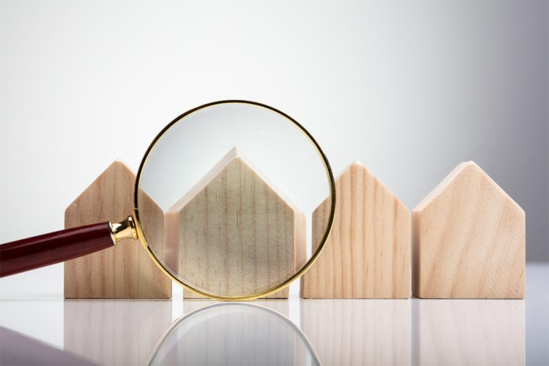 A magnifying glass in front of wooden house silhouettes arranged in a row