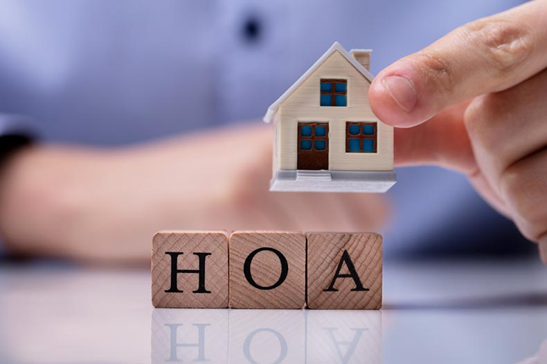A businessman's hand placing a house model on a wooden blocks spelling 'HOA'