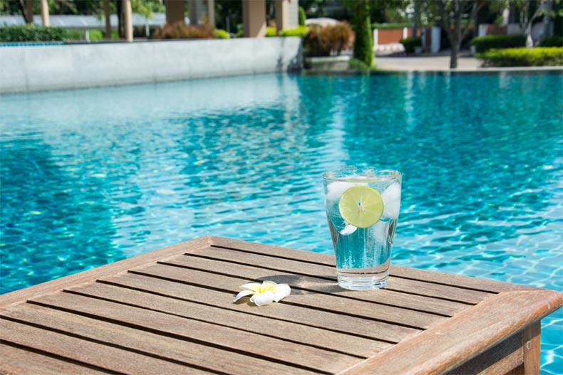 A glass of cold water with ice cubes and a slice of lime on wooden table by a swimming pool