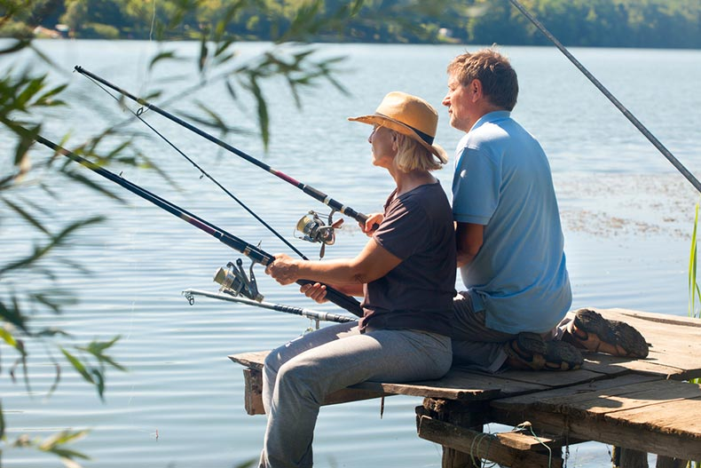 An older couple sitting on the end of a dock and fishing
