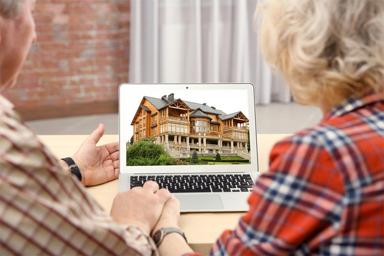 A senior couple looking for a house on a real estate market website