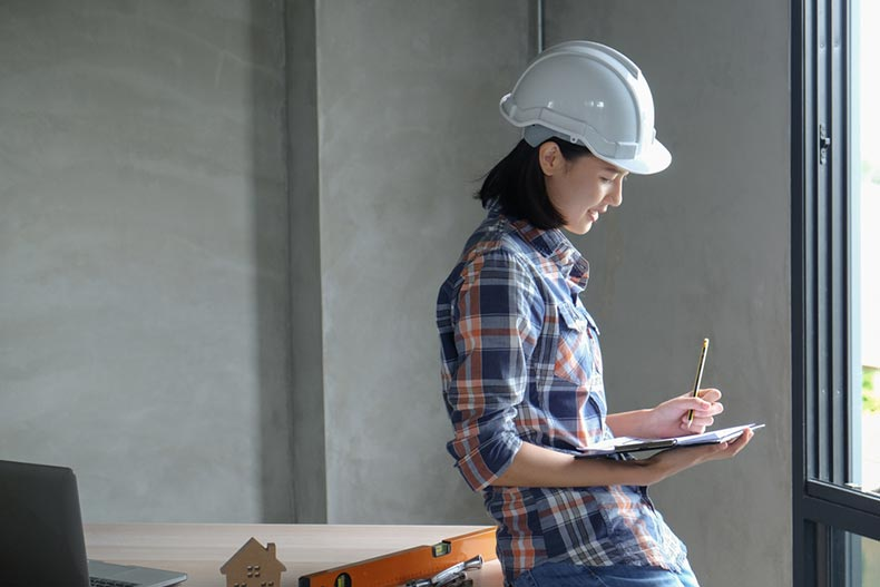 A home inspector wearing a hard hat and writing a report