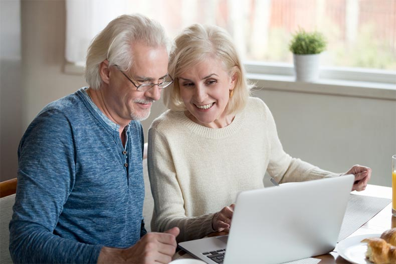 An older couple sitting at the breakfast table and smiling while shopping for homes online