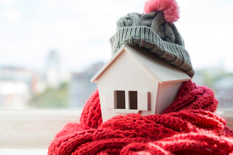 A wooden model of a house wearing a knitted cap and scarf