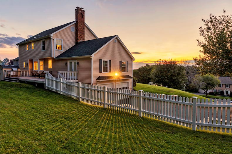 A white picket fence surrounding a beautiful colonial American house at sunset