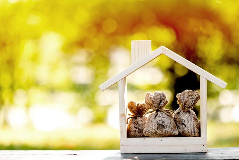 A small wooden house with sacks of money inside set in front of a warm background