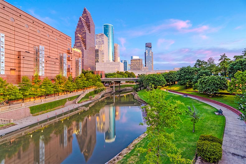 Tree-filled park with adjoining stream looking onto Downtown Houston at dusk