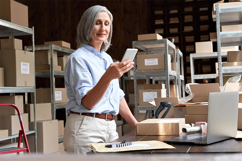 An older woman working in a warehouse and using a mobile app to check a parcel box